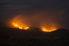 Burning mountains in the Maphutseng Valley, Mohale's Hoek, Lesotho. Shepherds often burn the mountain sides in Lesotho to promote growth of new grazing for their animals. Traditionally Basotho shepherds also use fire in this way to call on their ancestral gods to provide rain.